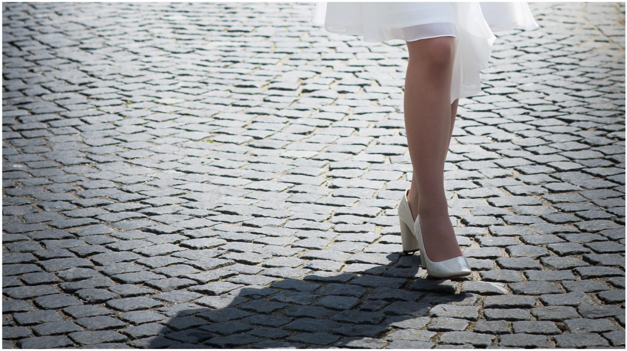 Beine von einer jungen Frau auf Pflastersteine