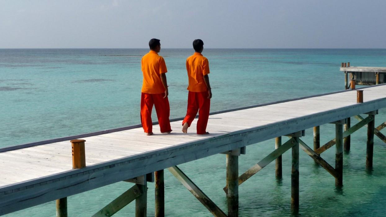 2 bunt gekleidete Männer auf einem Steg auf der Malediven. Fotograf Ulla Wälder